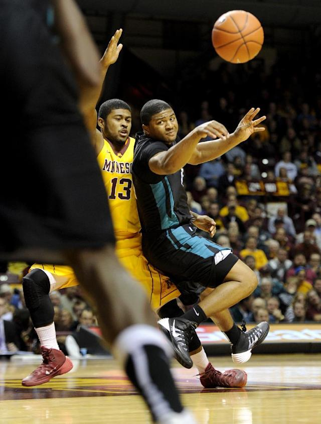 Minnesota guard Maverick Ahanmisi (13) guards against a pass by Coastal Carolina guard Eric Smith (5) during the first half of an NCAA college basketball game in Minneapolis on Tuesday, Nov. 19, 2013. (AP Photo/Hannah Foslien)