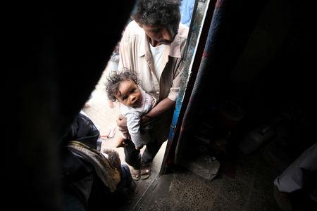 FILE PHOTO: A displaced man from Yemen's Red Sea port city of Hodeida holds his son as he stands at the door of a shelter in Sanaa, Yemen May 12, 2019. Picture taken May 12, 2019. REUTERS/Khaled Abdullah/File Photo