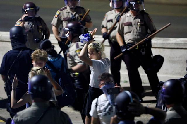 <p>A protester raises her hands after being contained by law enforcement, while being arrested during a march on Interstate 94 after a jury found St. Anthony Police Department officer Jeronimo Yanez not guilty of second-degree manslaughter in the death of Philando Castile, at the Minnesota State Capitol in St. Paul, Minnesota, U.S., June 16, 2017. Picture taken June 16, 2017. (Adam Bettcher/Reuters) </p>