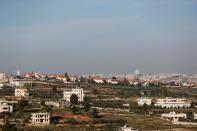 A view shows Palestinian houses as an Israeli settlement is seen in the background near Ramallah in the Israeli-occupied West Bank
