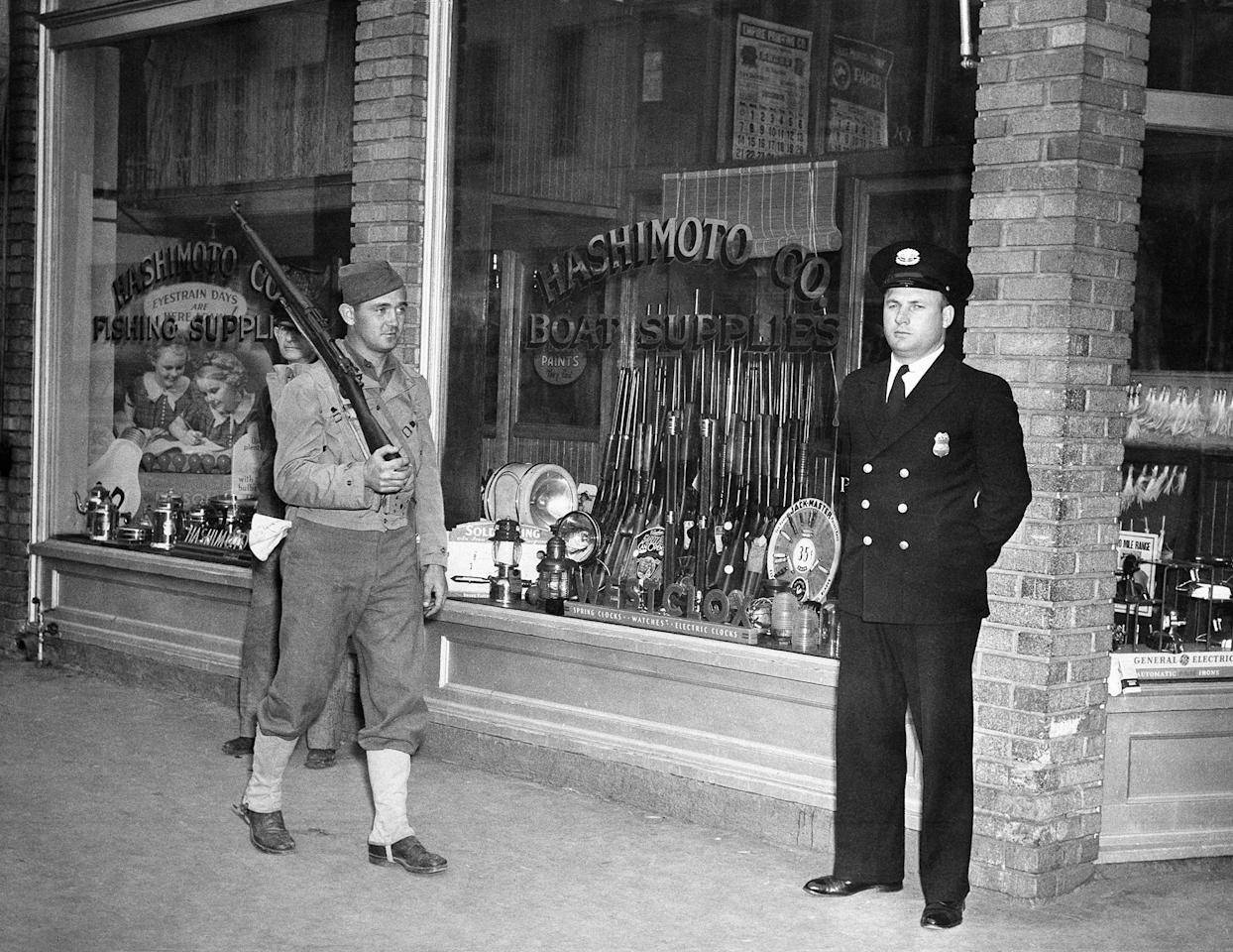<p>This Japanese small arms and boat hardware store on Terminal Island, San Pedro, Los Angeles, Calif., on which is a large Japanese community, was closed by the U.S. customs service, Dec. 8, 1941. Pvt. Anthony Prah, left, and Lewis C. Brown, of the customs service, was detailed to guard the establishment. In Washington, Treasury Secretary Henry Morgenthau announced seizure of all Japanese banks and business enterprises in the United States. (AP Photo) </p>