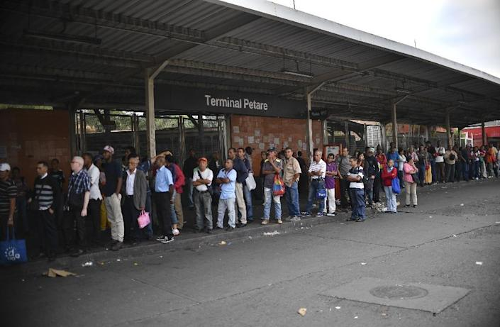 People wait for transportation at a bus station in Petare during a power outage in Caracas on March 26, 2019 (AFP Photo/Yuri CORTEZ)
