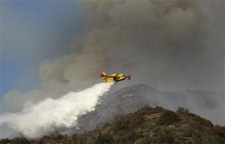 "An air tanker makes waters drops as firefighters battle a fast-moving California wildfire, so-called the ""Colby Fire"", in the hills of Glendora"
