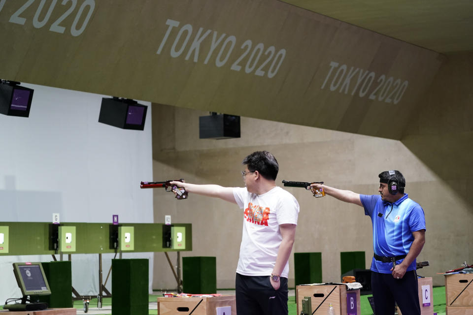 Pang Wei, left, of China, Javad Foroughi, of Iran, compete in the men's 10-meter air pistol at the Asaka Shooting Range in the 2020 Summer Olympics, Saturday, July 24, 2021, in Tokyo, Japan. Foroughi went on to win the gold medal, with Wei taking the bronze. (AP Photo/Alex Brandon)
