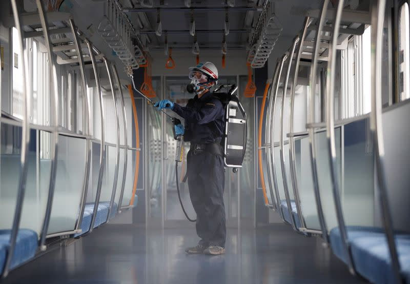 An employee of the Tokyo Metro sprays chemicals for anti-virus and bacteria coating in order to prevent infections following the coronavirus disease (COVID-19) outbreak in Tokyo