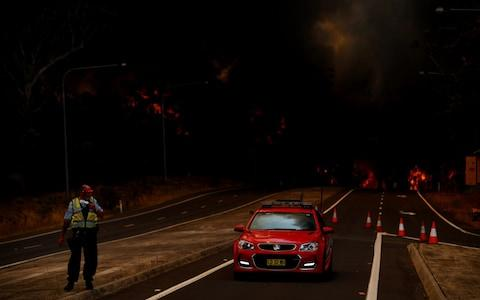 A police officer prepares to flee his roadblock in Sydney as the fire races towards him - Credit: SAM MOOY/GETTY IMAGES