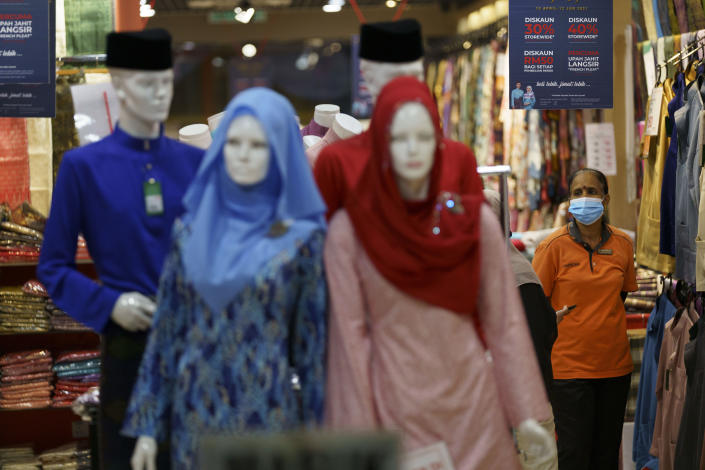 In this Saturday, April 24, 2021, photo, a clothing shop clerk wearing a protective mask waits for customers at the Ramadan bazaar in Kuala Lumpur, Malaysia. Malaysian Prime Minister Muhyiddin Yassin announced Monday that the whole country will be placed under a near lockdown for about a month but all economic sectors will be allowed to operate. (AP Photo/Vincent Thian)