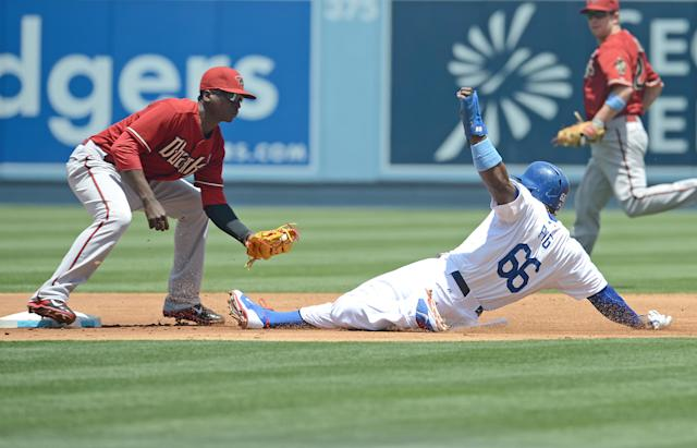 Arizona Diamondbacks' Didi Gregorius, left, tags out Los Angeles Dodgers' Yasiel Puig on a steal-attempt in the first inning a baseball game on Sunday, June 15, 2014, in Los Angeles. (AP Photo/Jayne Kamin-Oncea)