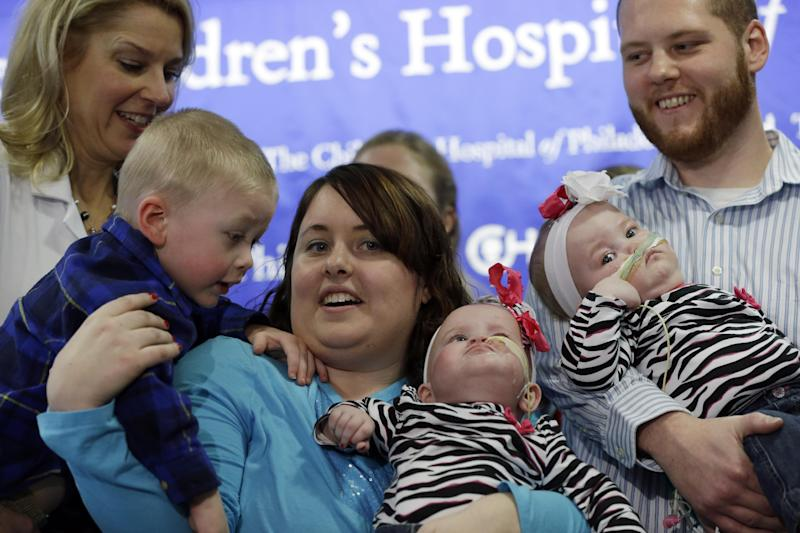 Shellie and Greg Tucker, along with their son Owen, 2, left, parents of Allison, center and Amelia, center right, present their nine-month-old girls who were formerly conjoined twins at Children's Hospital of Philadelphia (CHOP) Thursday, Dec. 20, 2012, in Philadelphia. Surgeons at CHOP separated the Tucker girls during a seven-hour operation in November. The infants from Adams, N.Y., had been joined at the lower chest and abdomen. They shared their chest wall, diaphragm, pericardium and liver. (AP Photo/Matt Rourke)
