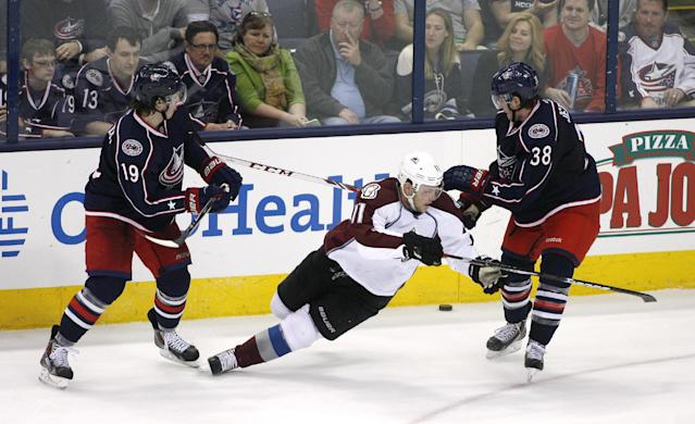 Colorado Avalanche's Jamie McGinn (11) loses his footing between Columbus Blue Jackets' Ryan Johansen (19) and Boone Jenner (38) during the third period of an NHL hockey game, Tuesday, April 1, 2014, in Columbus, Ohio. (AP Photo/Mike Munden)