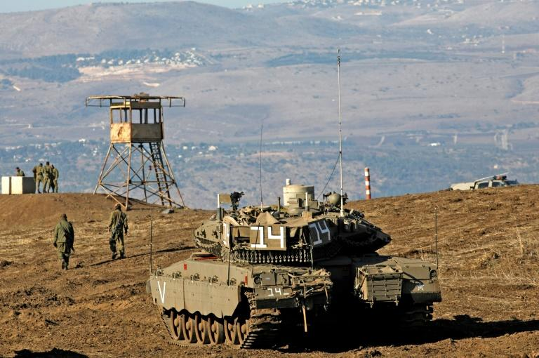 Israeli troops equipped with armoured vehicles survey neighbouring Syria from the Golan Heights, a strategic plateau Israel seized from Syria in the Six-Day War of 1967