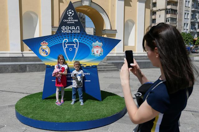 A woman takes a picture of children in front of the logo of the Champions League Final at the Independence Square in Kiev, Ukraine, May 10, 2018. Picture taken May 10, 2018. REUTERS/Valentyn Ogirenko