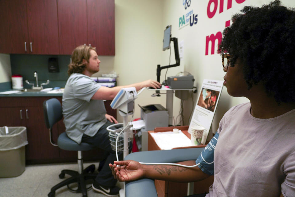 "In this Aug. 7, 2017, photo, Kenneth Parker Ulrich, left, a research technician at the University of Pittsburgh Medical Center, collects blood pressure data from Erricka Hager, a participant in the ""All of Us"" research program in Pittsburgh. The ""All of Us"" research program is run by the National Institutes of Health and plans to track the health of at least 1 million volunteers by 2019. By doing so, researchers hope to learn how to better tailor treatments and preventative care to people's genes, environments, and lifestyle. The University of Pittsburgh is running a pilot program with some of the first enrollees in the study. (AP Photo/Dake Kang)"