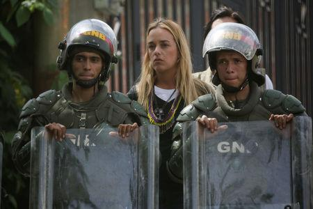 Venezuelan National Guards stand guard in front of Lilian Tintori (C), wife of jailed Venezuelan opposition leader Leopoldo Lopez, during a rally in support of political prisoners and against Venezuelan President Nicolas Maduro, outside the military prison of Ramo Verde, in Los Teques, Venezuela April 28, 2017. REUTERS/Marco Bello