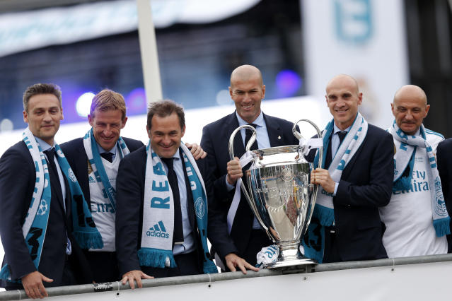 Real Madrid head coach Zinedine Zidane, third right, and his assistants pose with the trophy in Cibeles Square in Madrid, Spain, Sunday, May 27, 2018, to celebrate winning the Champions League final soccer match against Liverpool. (AP Photo/Francisco Seco)