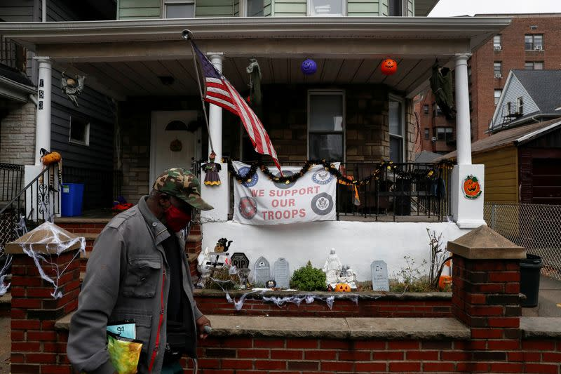 FILE PHOTO: A man wearing a protective face mask walks by the U.S. flag and Halloween decorations as the spread of coronavirus disease (COVID-19) continues in the borough of Brooklyn in New York