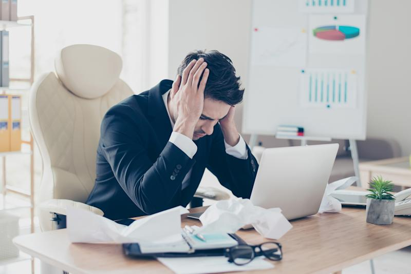 Portrait of exhausted sad nervous upset desperate marketer accountant freelancer holding head thinking about problems sitting at table with crumbled paper documents