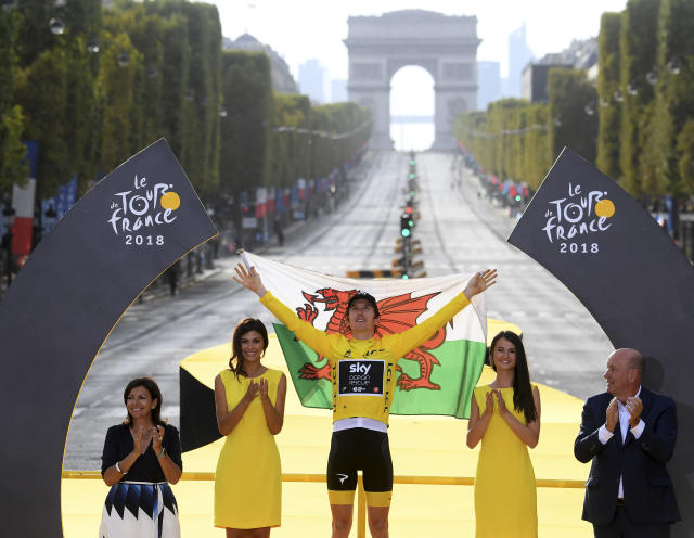 Tour de France winner Britain's Geraint Thomas, wearing the overall leader's yellow jersey, and draped in the flag of Wales celebrates on the podium after the twenty-first stage of the Tour de France cycling race over 116 kilometers (72.1 miles) with start in Houilles and finish on Champs-Elysees avenue in Paris, France, Sunday July 29, 2018. (Stephane Mantey, pool via AP)