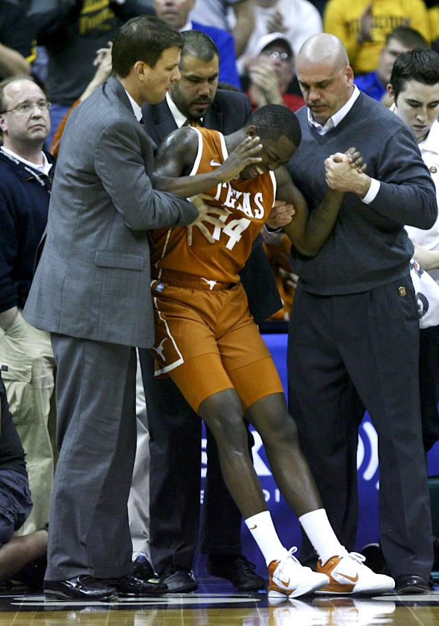 KANSAS CITY, MO - MARCH 09: J'Covan Brown #14 of the Texas Longhorns is helped to his feet after being injured while playing against the Missouri Tigers in the second half during the semifinals of the Big 12 Basketball Tournament March 09, 2012 at Sprint Center in Kansas City, Missouri. (Photo by Ed Zurga/Getty Images)