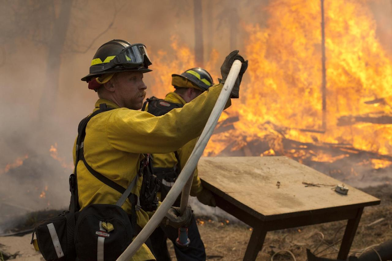 Central Emergency Services firefighter Dan Jensen maneuvers a hose into position to fight a portion of a wildfire Sunday, May 25, 2014, in the Funny River community of Soldotna, Alaska. A massive wildfire pushed by wind in Alaska's Kenai Peninsula south of Anchorage continued to explode in size, leading to mandatory evacuations of 1,000 structures, officials said Sunday. (AP Photo/Peninsula Clarion, Rashah McChesney)