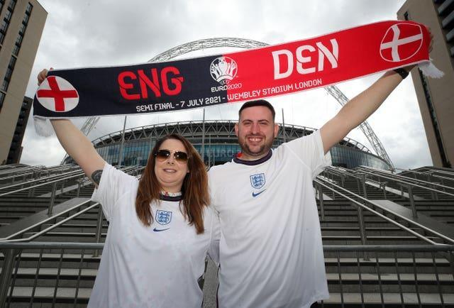 Two England fans stand outside Wembley with a half-and-half scarf (Nick Potts/PA)