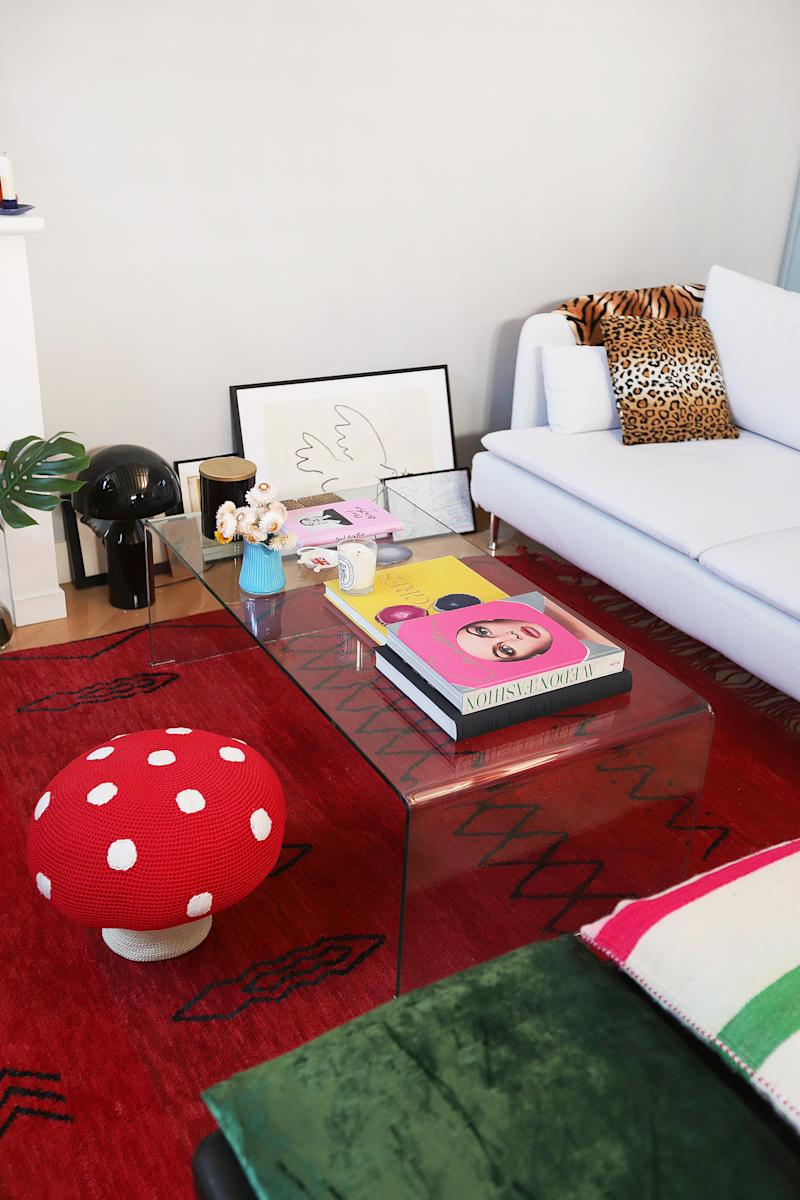 The vintage mushroom bench pulls together the red Berber rug from Marrakech and the white IKEA sofa. The acrylic coffee table displays Lucia and Helena's favorite fashion tomes.