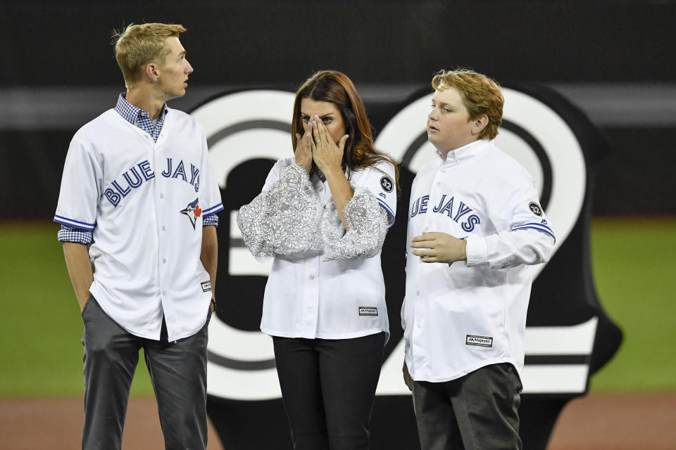 Roy Halladay's family, son Braden (L), wife Brandy and other son Ryan take in the emotion during a ceremony honoring the late pitcher by retiring his No. 32 on opening day. (Getty Images)