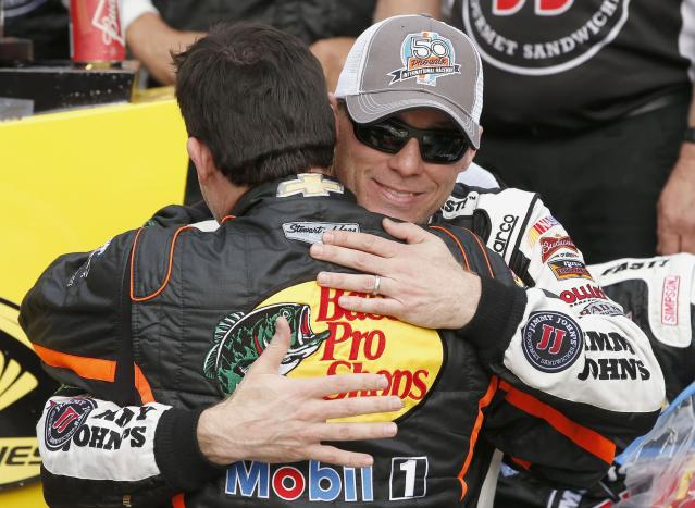 Kevin Harvick, right, gets a hug from Tony Stewart after Harvick woin the NASCAR Sprint Cup Series auto race Sunday, March 2, 2014, in Avondale, Ariz. (AP Photo/Ross D. Franklin)