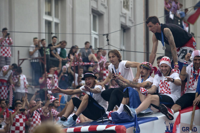 Croatia's national soccer team members are seen on top of an open bus as they are greeted by fans during a celebration in central Zagreb, Croatia, Monday, July 16, 2018. In an outburst of national pride and joy, Croatia rolled out a red carpet and staged a euphoric heroes' welcome for the national team on Monday despite its loss to France in the World Cup final. (AP Photo/Marko Drobnjakovic)