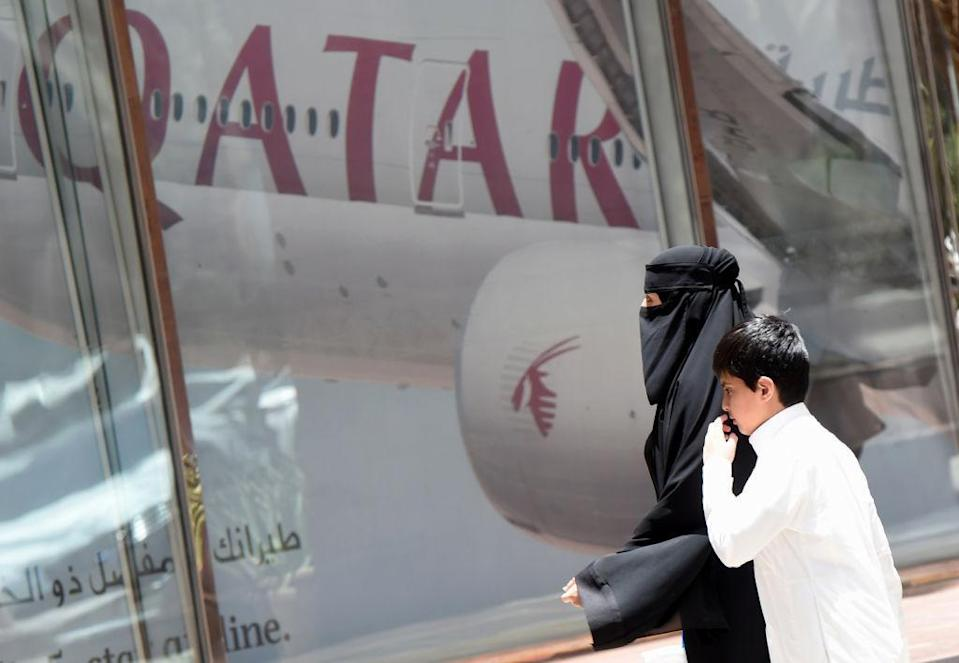A woman and boy walk past a Qatar Airways branch in the Saudi capital of Riyadh on 5 June 2017 (AFP/Getty Images)