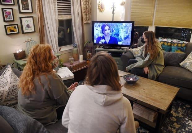 Millions of people around the world watched the interview. This photo illustration shows people in masks in Arlington, Va., watching on March 7.