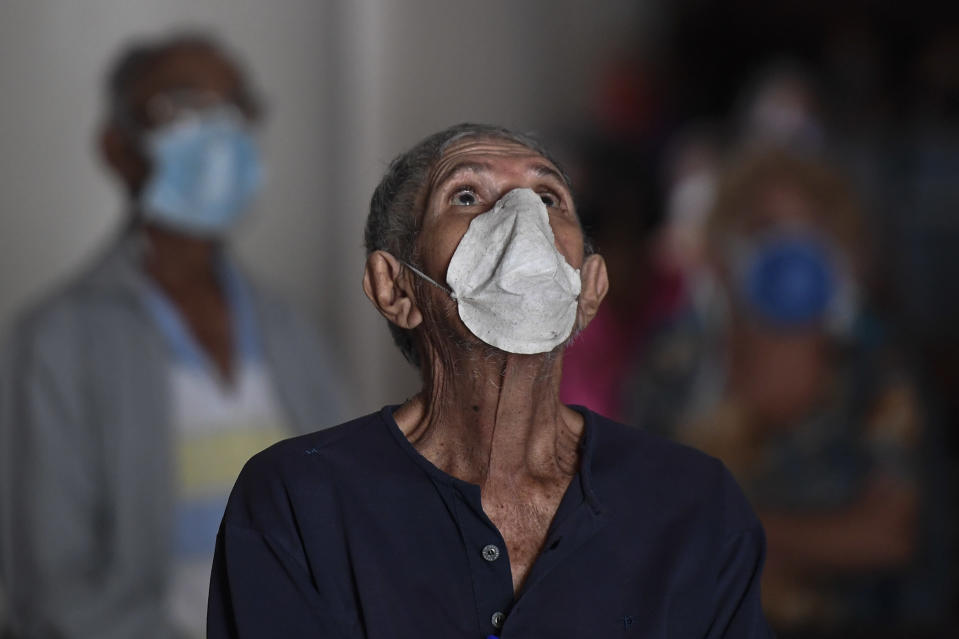 An elderly man, wearing a protective face mask as a precaution against the spread of the new coronavirus, prays during mass at a church in Caracas, Venezuela, Sunday, March 29, 2020. COVID-19 causes mild or moderate symptoms for most people, but for some, especially older adults and people with existing health problems, it can cause more severe illness or death. (AP Photo/Matias Delacroix)