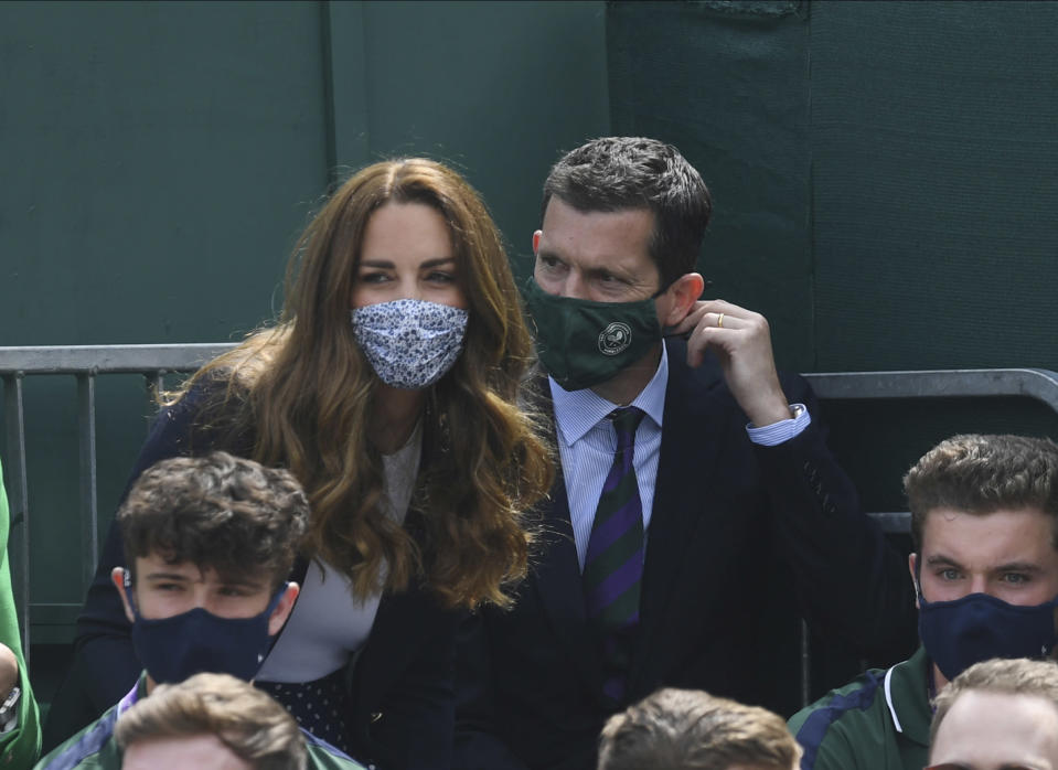 Britain's Kate, Duchess of Cambridge takes her on seat on Court 14 next to Tim Henman to watch the men's doubles match between Britain's Jamie Murray and Brazil's Bruno Soares against Nicholas Monroe of the US and Canada's Vasek Pospisil on day five of the Wimbledon Tennis Championships in London, Friday July 2, 2021. (Neil Hall/Pool via AP)