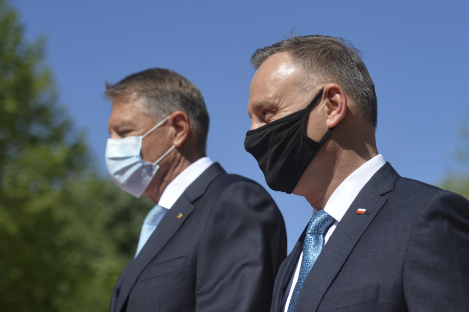Polish President Andrzej Duda, right, reviews the honor guard with Romanian President Klaus Iohannis during the welcoming ceremony at the Cotroceni presidential palace in Bucharest, Romania, Monday, May 10, 2021. (AP Photo/Alexandru Dobre)