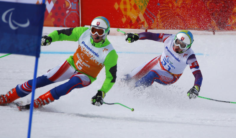 Miroslav Haraus of Slovakia, right, and his guide Maros Hudik race to win 2nd place in the men's downhill, visually impaired event at the 2014 Winter Paralympic, Saturday, March 8, 2014, in Krasnaya Polyana, Russia. (AP Photo/Dmitry Lovetsky)