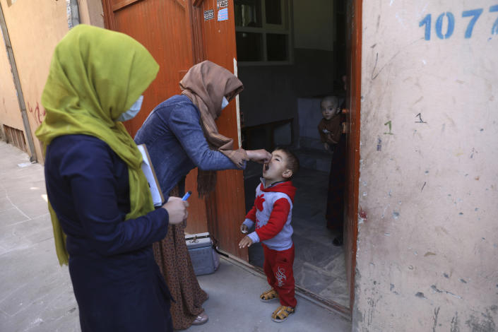 Health workers administer a polio vaccine to a child during a polio vaccination campaign in the city of Kabul, Afghanistan, Tuesday, March 30, 2021. Three female polio vaccinators were gunned down in separate attacks Tuesday in eastern Afghanistan, provincial officials said. (AP Photo/Rahmat Gul)