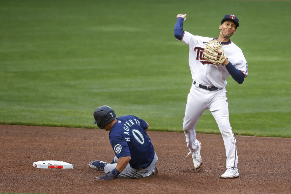 Minnesota Twins shortstop Andrelton Simmons throws to first after forcing out Seattle Mariners' Sam Haggerty, for a double play on a ball hit by J.P. Crawford during the seventh inning of a baseball game Thursday, April 8, 2021, in Minneapolis. The Twins won 10-2. (AP Photo/Bruce Kluckhohn)
