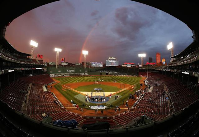 IN this image taken with a fisheye lens, Boston Red Sox players take batting practice as a rainbow appears in the sky above Fenway Park Tuesday, Oct. 22, 2013, in Boston. The Red Sox are scheduled to host the St. Louis Cardinals in Game 1 of baseball's World Series on Wednesday. (AP Photo/Elise Amendola)