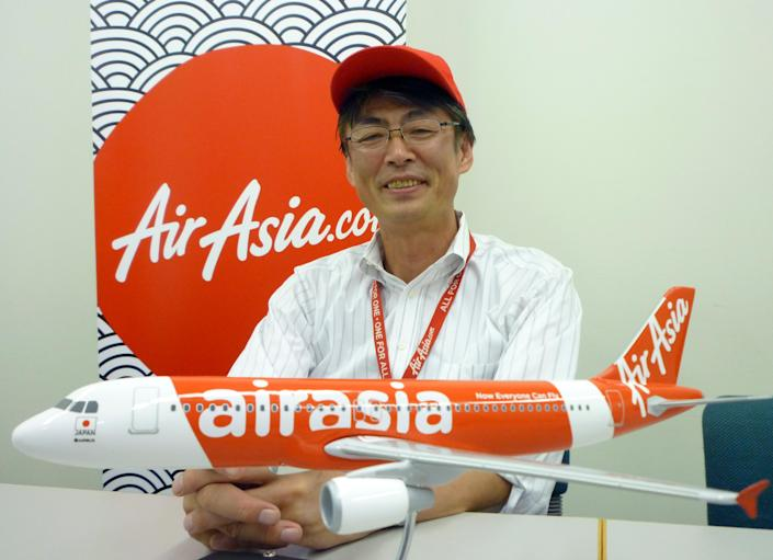 """In this Sept. 28, 2012 photo, AirAsia Japan President Kazuyuki Iwakata speaks during an interview in Tokyo. """"It's not that the meals on standard fares were ever free. The charge was just part of the ticket price,"""" Iwakata told The Associated Press. """"With us, people pay only for what they need."""" As a marketing ploy, AirAsia Japan, which started operations in August, offered tickets for just 5 yen (5 cents) to the first 10,000 people. They quickly sold out. (AP Photo/Yuri Kageyama)"""