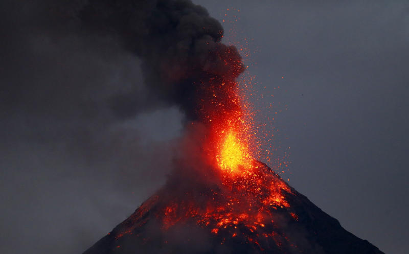 Mayon volcano spews red-hot lava in another eruption as seen from Legazpi city, Albay province, roughly 200 miles (340 kilometers) southeast of Manila, Philippines, Tuesday, Jan. 23, 2018. Mayon has spewed fountains of red-hot lava and massive ash plumes anew in a dazzling but increasingly dangerous eruption that has sent 56,000 villagers fleeing to evacuation centers. (AP Photo/Bullit Marquez)