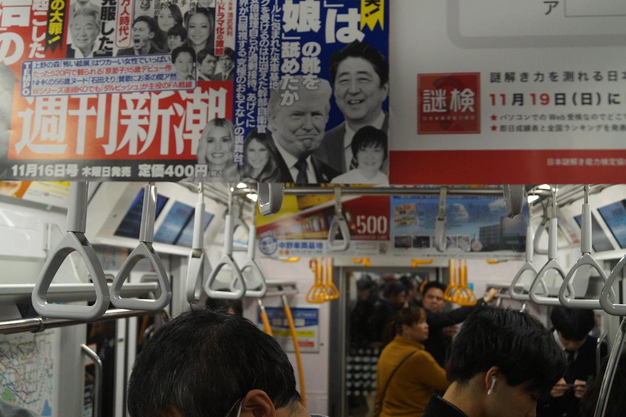 A subway advertisement for a weekly magazine features Japanese Prime MinisterShinzo Abe, his wife, Akie Abe, U.S. President Trump, first lady Melania Trump and first daughter Ivanka Trump. The ad claims the American, Chinese and Korean media are laughing at the excessive hospitality Abe showed the Trump family. (Photo: Michael Walsh/Yahoo News)