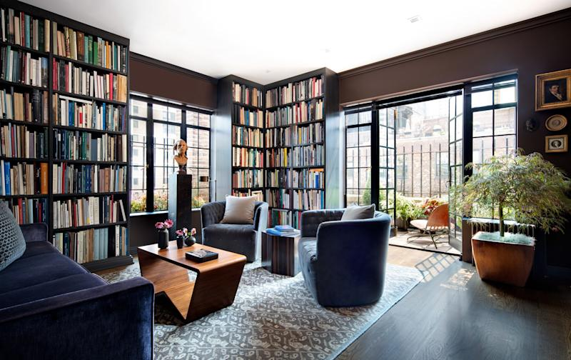 Floor-to-ceiling cerused-oak shelves in the library of a NYC apartment designed by Richard Rabel showcase clients Alan Wintermute and Colin Bailey's collection of important and rare art books. Furnishings include custom-made swivel chairs upholstered in a Donghia linen and a custom sofa—covered in a purple velvet from Pollack—that converts into a queen-size bed for guests. The American walnut cocktail table is from Dennis Miller Associates, and the side table is by Stéphane Parmentier from Maison Gerard.