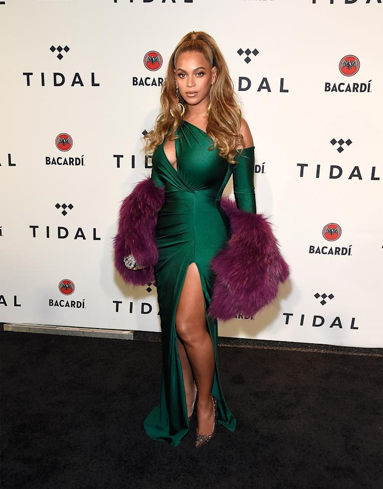 <p>Queen B stunned in a slinky emerald gown by Walter Mendez paired with a glamorous purple fur stole.<br /><i>[Photo: Getty]</i> </p>