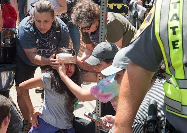 <p>People receive first-aid after a car accident ran into a crowd of protesters in Charlottesville, Va., on Aug. 12, 2017. (Photo: Paul J. Richards/AFP/Getty Images) </p>