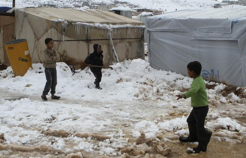 A Syrian refugee child shovels snow outside a tent in Aarsal town in Lebanon's eastern Bekaa