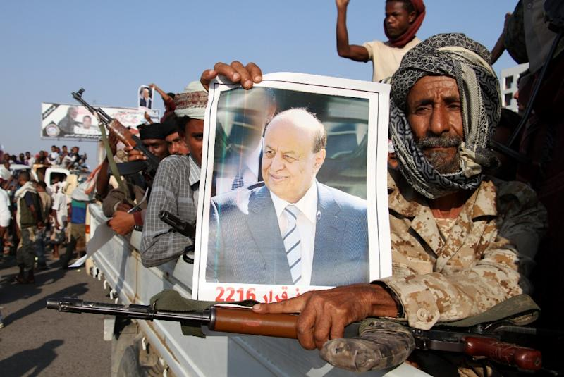 A man holds a portrait of Saudi-backed Yemeni President Abd Rabbo Mansour Hadi as thousands demonstrate in Aden against a new UN plan to end the devastating conflict (AFP Photo/Saleh Al-Obeidi)