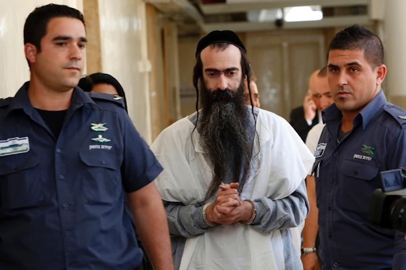Israeli ultra-Orthodox Jew Yishai Shlissel (C) is brought handcuffed to the Jerusalem Magistrate's Court on July 31, 2015 (AFP Photo/Gali Tibbon)