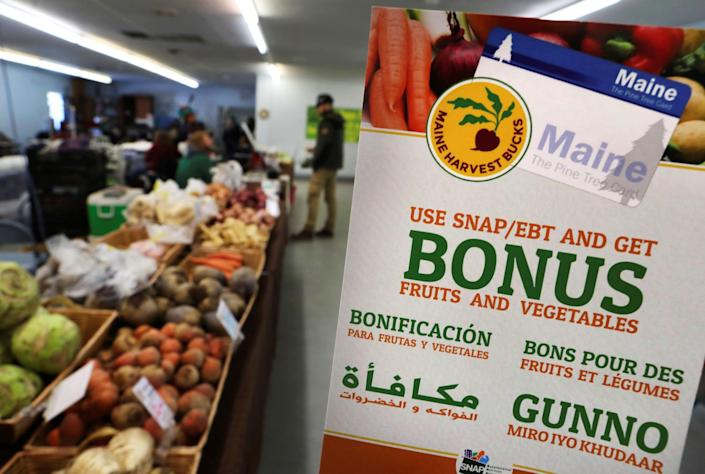 In this Friday, March 17, 2017, file photo, a sign advertises a program that allows food stamp recipients to use their EBT cards to shop at a farmer's market in Topsham, Maine. While many supermarkets and discounters accept SNAP benefits, many do not offer online grocery services amid the pandemic.