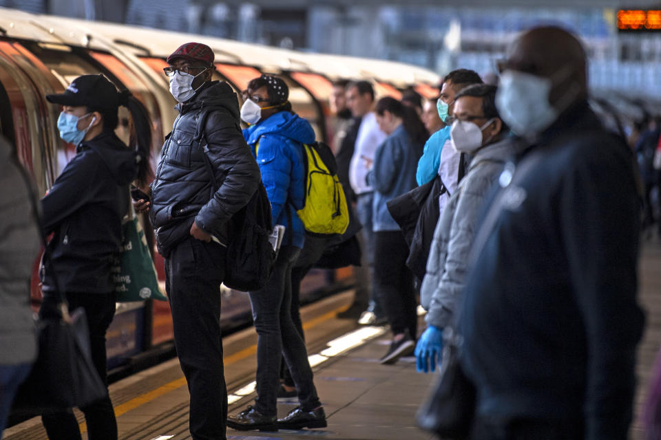 Passengers wearing face masks on a platform at Canning Town underground station in London. (Photo by Victoria Jones/PA Images via Getty Images)