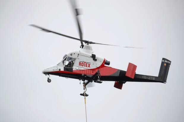 A Kaman K-Max K-1200 helicopter is pictured during tree felling works in Zurich, Switzerland on Dec. 17, 2019. A K-Max helicopter similar to the one pictured crashed on B.C.'s Sunshine Coast on Monday. (Arnd Wiegmann/REUTERS - image credit)
